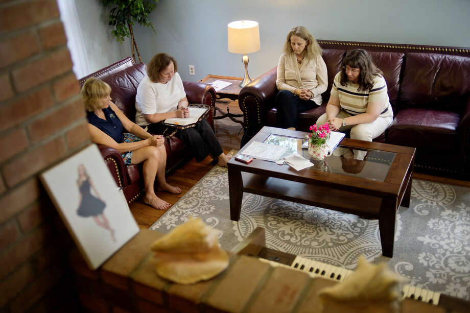 From left, Elizabeth Scott, Joan Grady, Carol Cushman and Doreen Keptner pray in Scott's Midland home during a meeting of Moms In Prayer on Monday evening. Photo: NICK KING | Nking@mdn.net