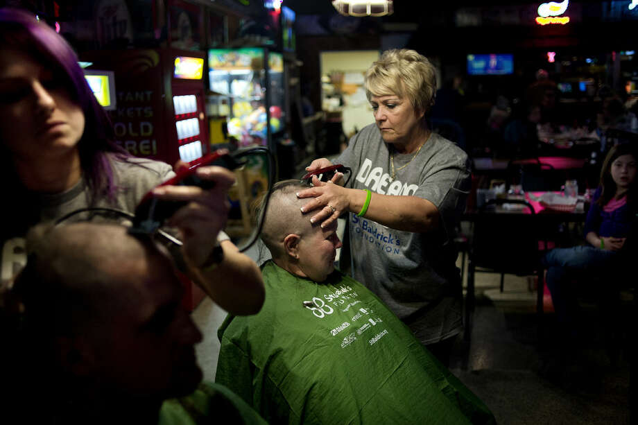 Wilma O'Dell, right, shaves the head of Denise Cole, lead medic at MidMichigan Medical Center-EMS, as O'Dell's coworker at Salon 45, Aleisha VanHorn, left, shaves the head of Midland firefighter Jacob Keister during the St. Baldrick's fundraiser on Saturday at The Boulevard Lounge in Midland. Photo: Nick King | Nking@mdn.net