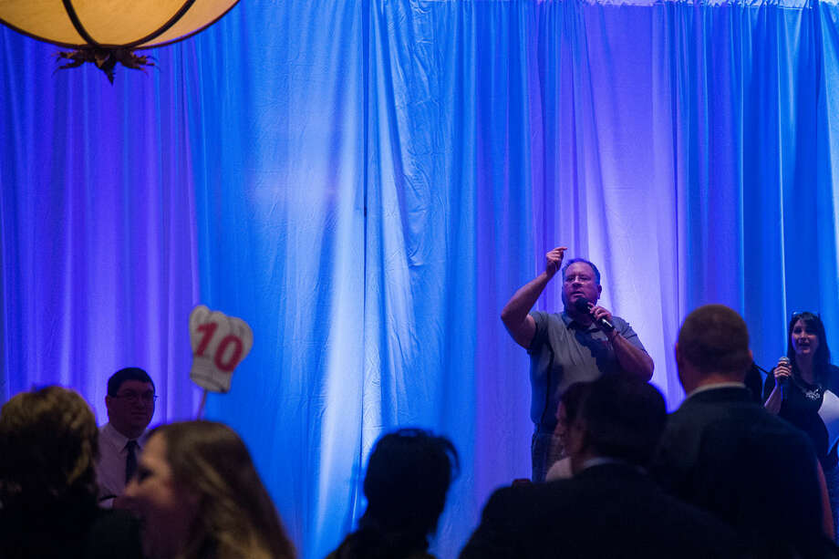 """Jerry O'Donnell, the """"Voice of Dow Diamond,"""" leads an auction during the Chefs for Shelterhouse fundraiser at the Great Hall Banquet and Convention Center in Midland on Thursday evening. Shelterhouse works to eliminate domestic and sexual violence. Photo: Zack Wittman 