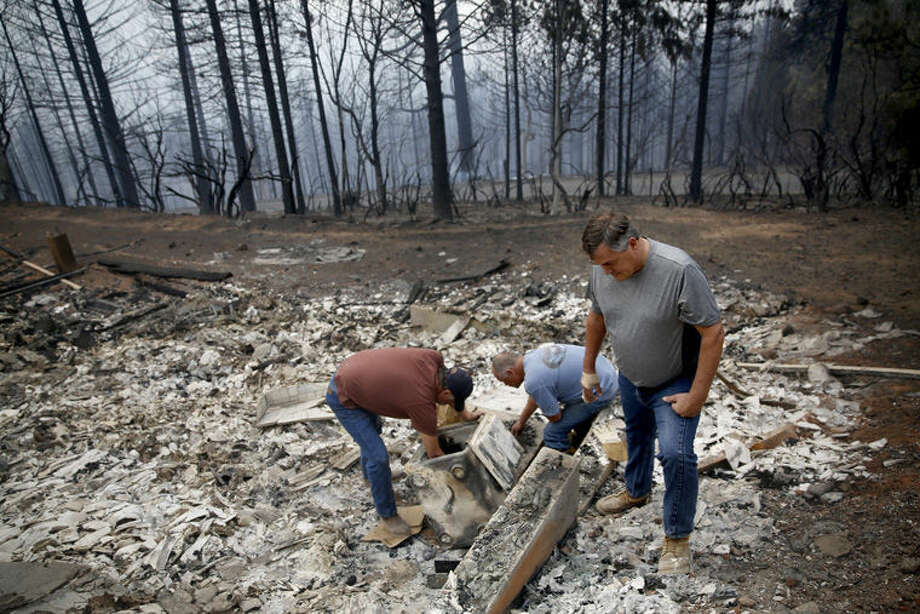 Homeowner John Flynn, left, and his friends Richard Hinchcliff, center, and Lake County District Attorney Don Anderson, right, look through burned the contents of his fire safe at his Summit Drive home in Cobb, Calif., Monday. Two of California's fastest-burning wildfires in decades overtook several Northern California towns, killing at least one person and destroying hundreds of homes and businesses. Photo: Beth Schlanker | The Press Democrat Via AP