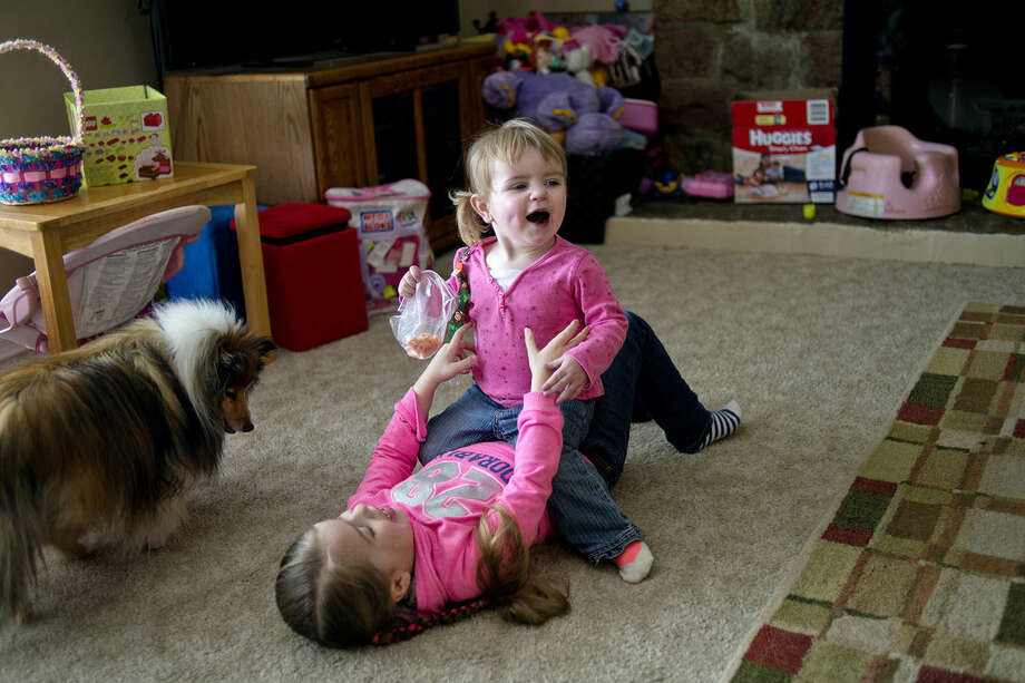Emerson Thompson, who will be 2 this month, sits on her sister, Faith, 5, as the family dog Molly looks on while the two play at their home on Saturday in Clare. Emerson has hypoplastic right heart syndrome, a congenital heart defect. Photo: NICK KING | Nking@mdn.net