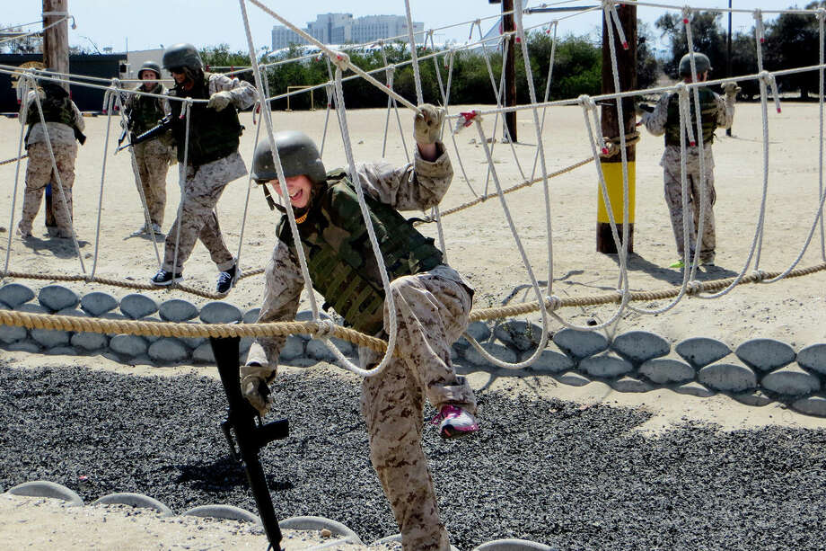 Dana Wyant, an English teacher from Muskegon, crosses a rope bridge during a bayonet course at Marine Corps Recruit Depot in San Diego, Calif. Photo: Matthew Woods | Mwoods@mdn.net