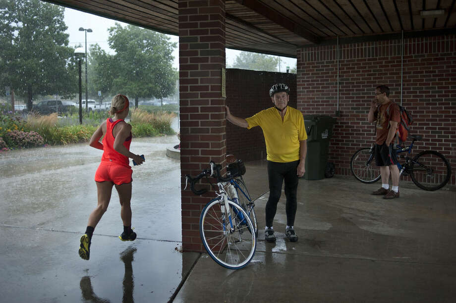 "Jasmine Ortmann, left, of Midland runs circles around the Farmers Market awning while Tom Young of Auburn and Jason Booth of Midland wait for the rain to subside Thursday. ""I was trying to get in 12 miles today,"" Ortmann, who is training for the Detroit marathon, said. Photo: Brittney Lohmiller 