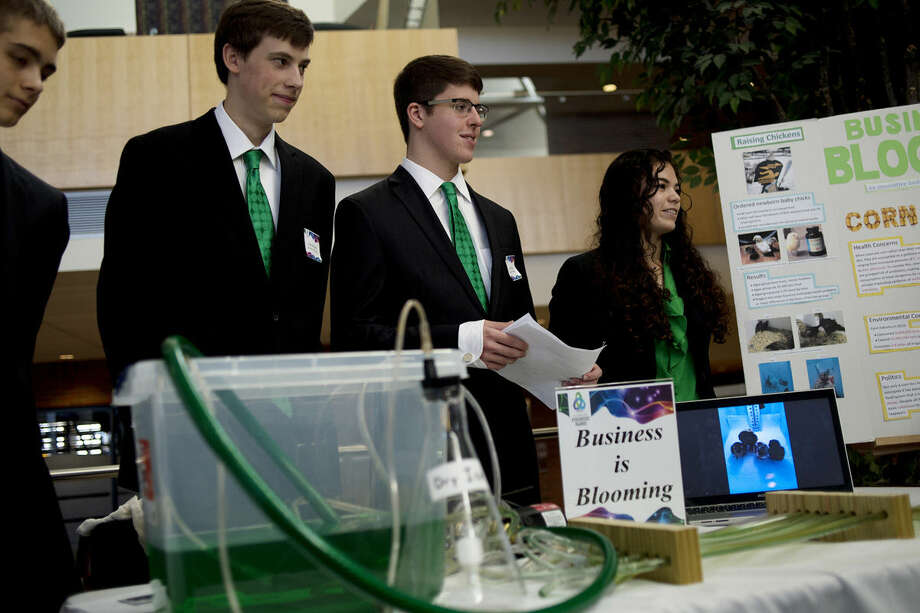 From left, Dow High seniors and members of the Business is Blooming team Griffin Kendziorski, Jackson Storer, Fritz Hyde and Jasmine Purtell stand with their project which looked at creating a way to grow and use algae as a food source for agricultural animals. Photo: Nick King | Nking@mdn.net