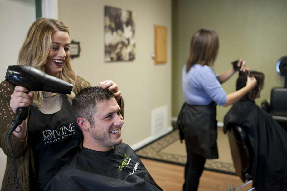 BRITTNEY LOHMILLER | blohmiller@mdn.net Cari Rynearson, left, dries Auburn's Cody Baranowski's hair at Divine Beauty Studio. Divine Beauty Studio is the winner of the Reader's Choice for best beauty salon. Photo: Brittney Lohmiller/Midland Daily News