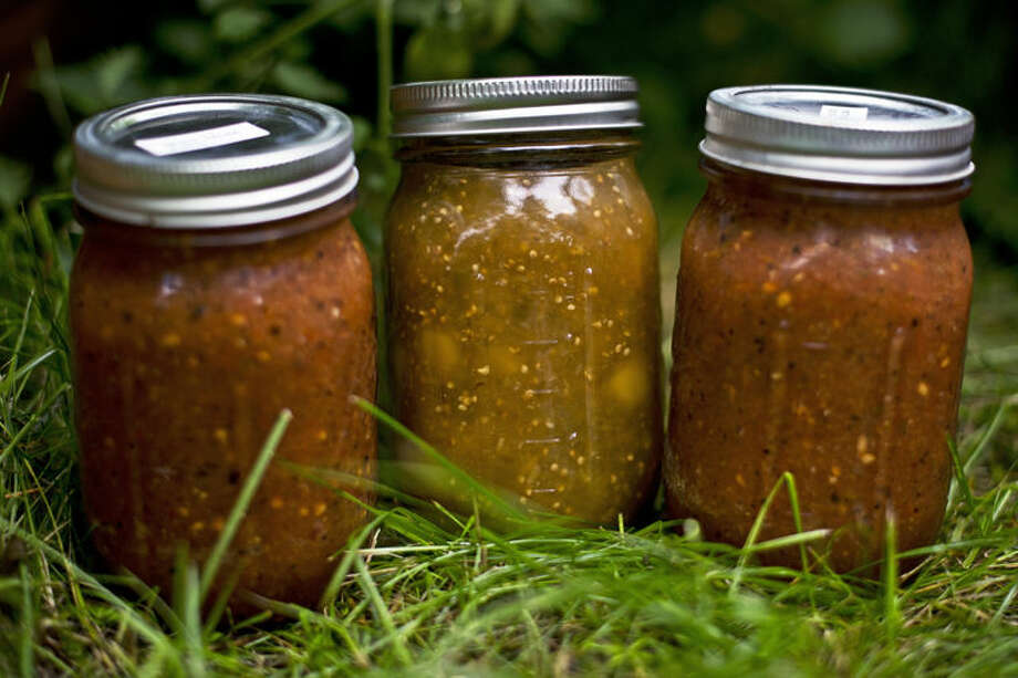 Two jars of spicy salsa and another of tomatillo mango sit outside Carole and Kim Donaghy's garden  in Midland. The Donaghys have been harvesting their garden and turning it into homemade salsa for four years due to Kim's love for Mexican food. The couple makes two types per year — one a fruit-based and the other a traditional spicy. They give away their product to family and friends. Photo: Erin Kirkland/Midland Daily News