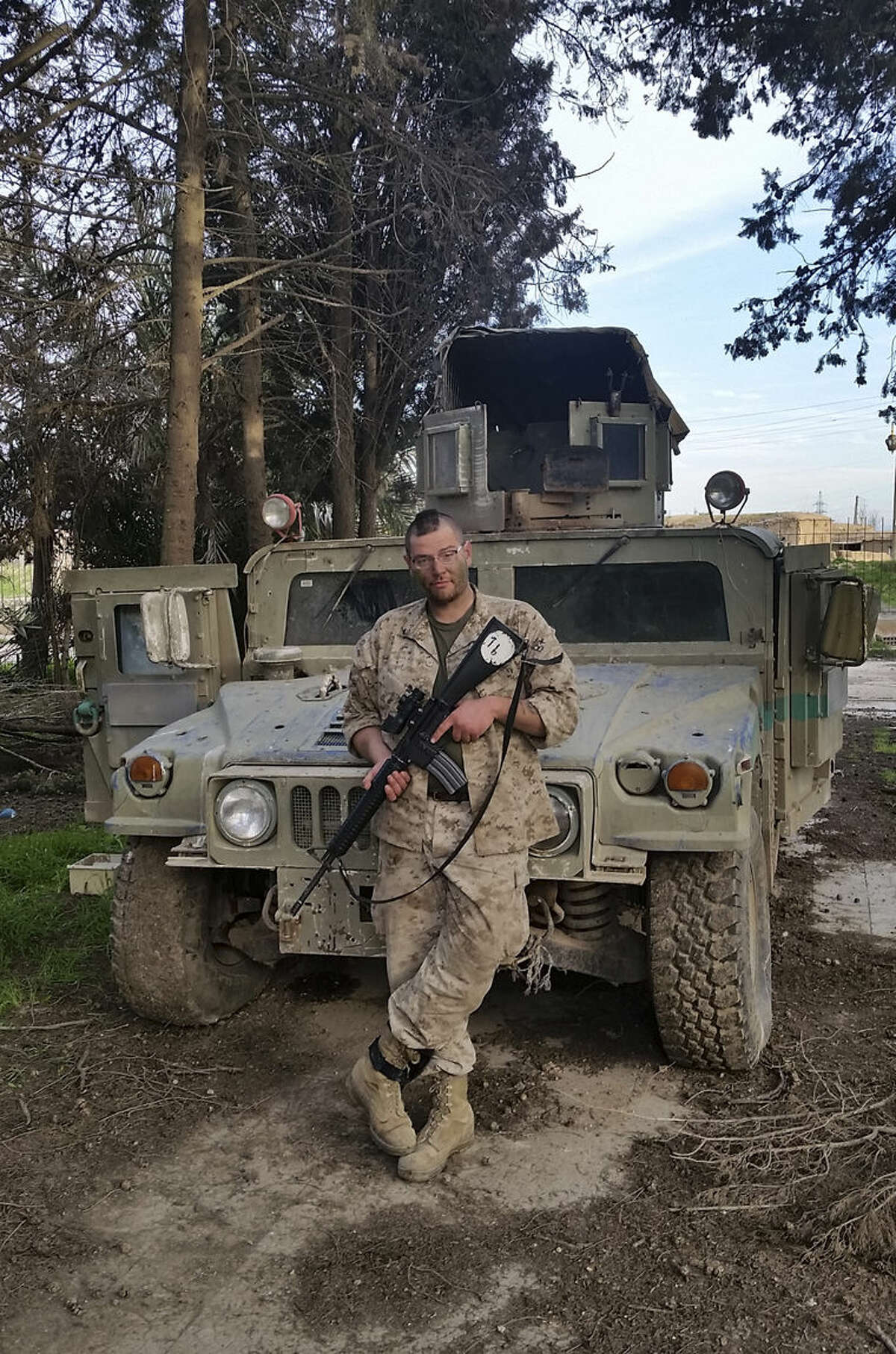 In this Feb. 26, 2015 photo, Jamie Lane, 29, an American veteran from Mount Pleasant, poses for a picture in front of an Iraqi Army Humvee captured and later abandoned by Islamic State militants in Tel Hamis, Syria. Lane is among a growing number of Iraq war veterans returning to the battlefield, this time without the American military, to join in the fight against the Sunni militants who now hold territory in a third of Iraq and Syria.