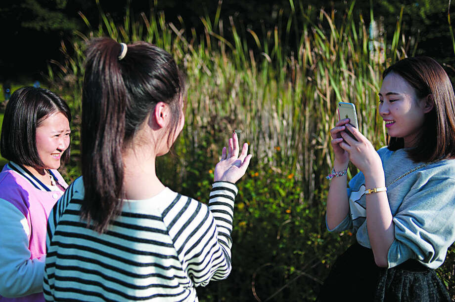 "BRITTNEY LOHMILLER | blohmiller@mdn.net Saginaw Valley State University English language program international students Biyuan Lou, from left, watches as a dragonfly lands on Jinuo Wang's hand and Wenwen Zheng takes a picture Thursday evening at Colette Urian's home in Sanford. This is the fifth year that Urian and her husband, Philip, hosted students at their home. ""For many students this is the first time they've gotten to see what American homes look like,"" Urian said. Photo: Brittney Lohmiller/Midland Daily News"