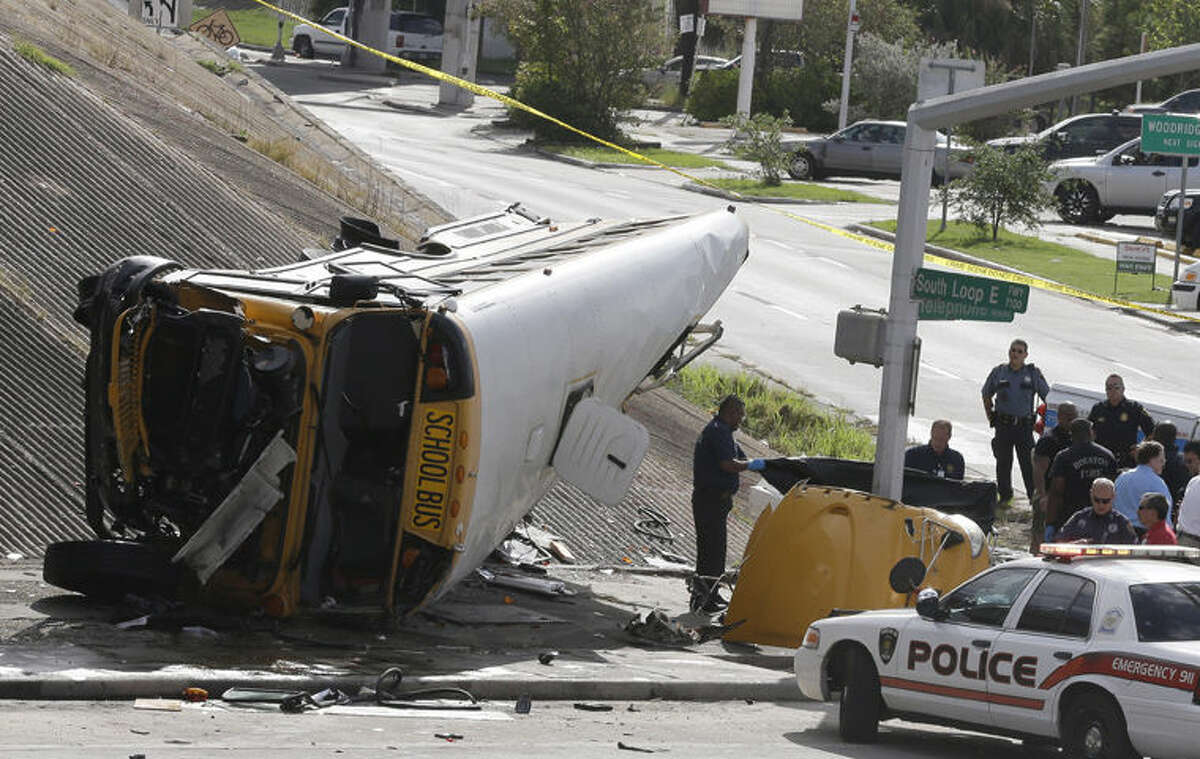 Investigators work around a Houston school bus, left, after it drove off a highway overpass on Tuesday in Houston, killing two students and seriously injuring three other people.