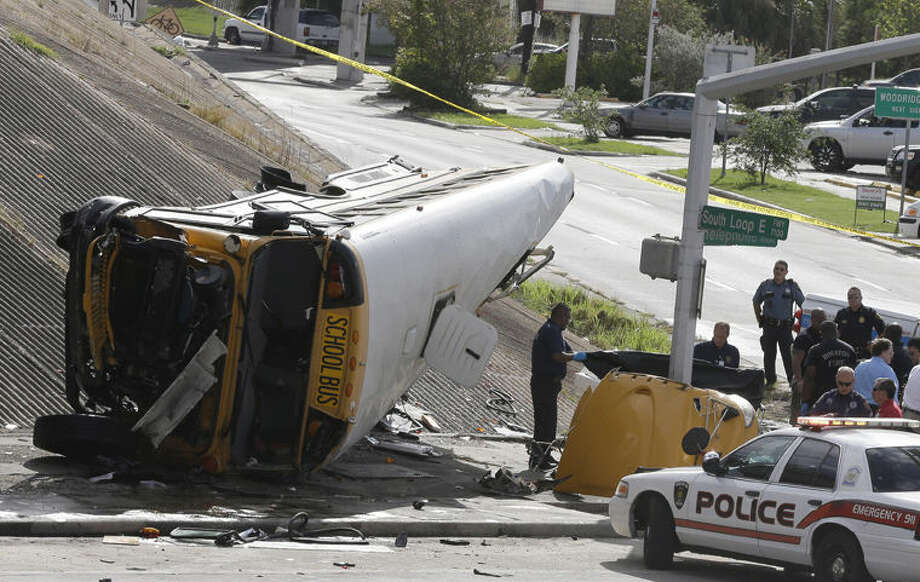 Investigators work around a Houston school bus, left, after it drove off a highway overpass on Tuesday in Houston, killing two students and seriously injuring three other people. Photo: Pat Sullivan | AP Photo