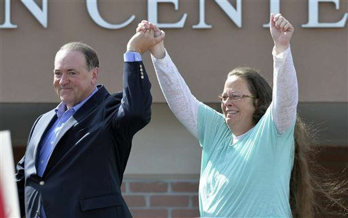 In this Sept. 8, 2015, file photo, Rowan County Clerk Kim Davis, with Republican presidential candidate Mike Huckabee at her side, greets the crowd after being released from the Carter County Detention Center, in Grayson, Ky. Davis, a longtime Democrat, says she is switching to the Republican Party because she feels abandoned by Democrats in her fight against same-sex marriage.
