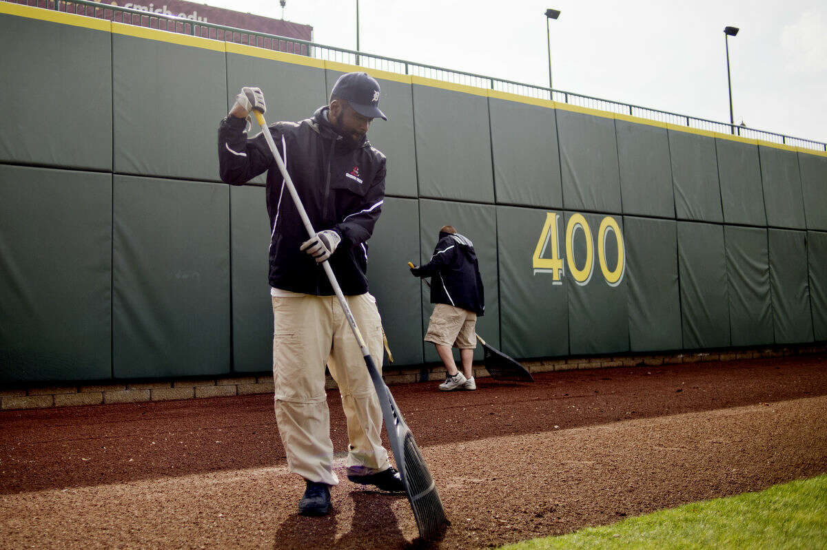 Great Lakes Loons grounds crew member Shannon Westbrook rakes the dirt in the outfield at Dow Diamond on Thursday as the crew prepares for the Loons opening day on Thursday, April 9.