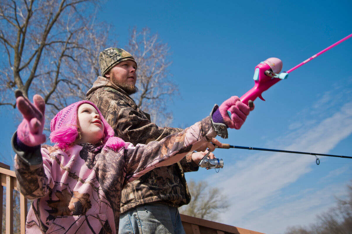 Kylah Brown, 6, casts her pink fishing rod with her father, Tom Brown of Port Sanilac, at Festival Park along the Tittabawassee River during the Freeland Walleye Festival on Saturday. Kylah had caught the first fish of the day out of their fishing group of family and friends. Tom Brown said it was his fifth year at the tournament, but the first time bringing Kylah.