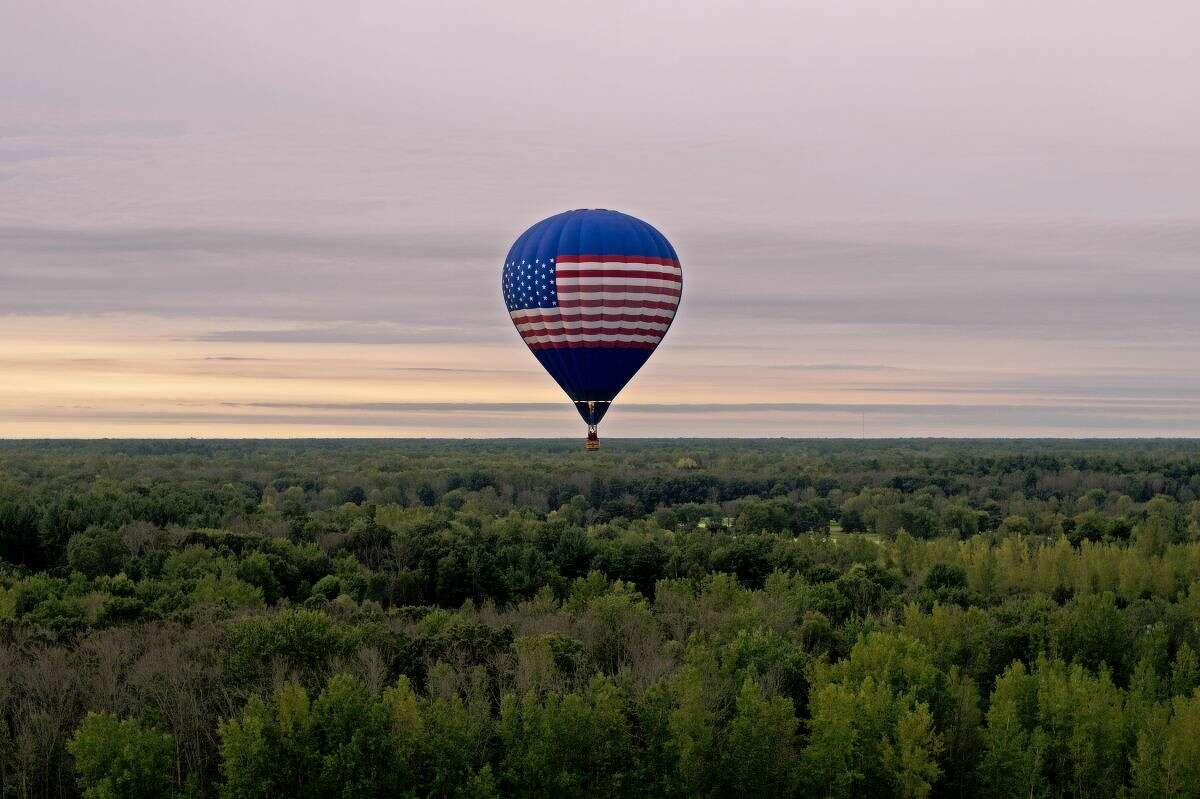 Altitude Endeavors pilot Phil Clinger of Battle Creek flies over Midland on Friday after taking off from the Midland County Fairgrounds. Clinger's early morning flight was part of the 2015 Midland Balloon Festival festivities.