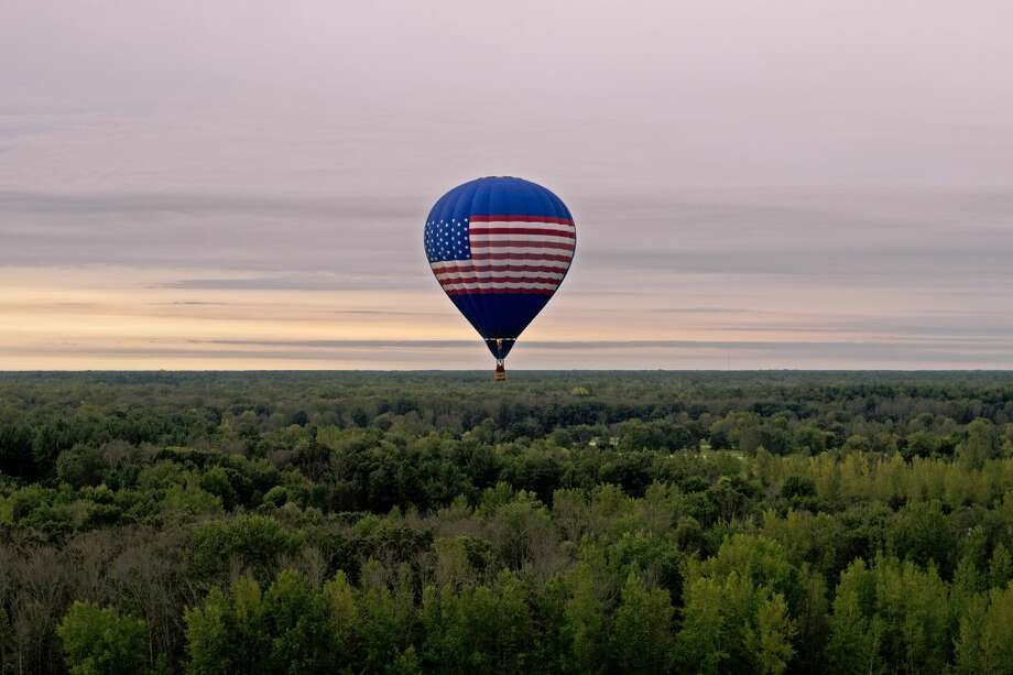 Altitude Endeavors pilot Phil Clinger of Battle Creek flies over Midland on Friday after taking off from the Midland County Fairgrounds. Clinger's early morning flight was part of the 2015 Midland Balloon Festival festivities. Photo: Erin Kirkland | Midland Daily News