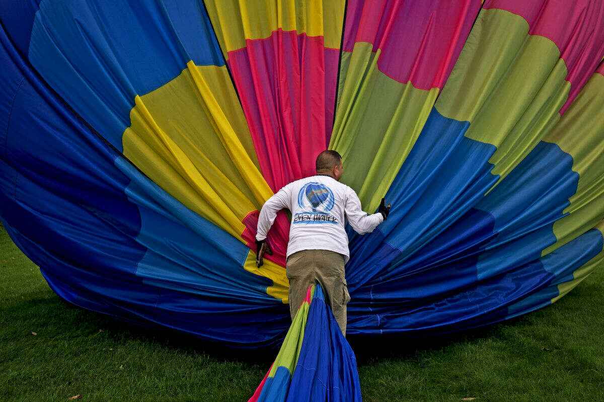 Winds of Freedom pilot Deven Cook of Battle Creek packs up his balloon after a ride from the Midland County Fairgrounds to Currie Golf Course on Friday. Cook has been flying and participating in the Midland Balloon Festival since 2009.