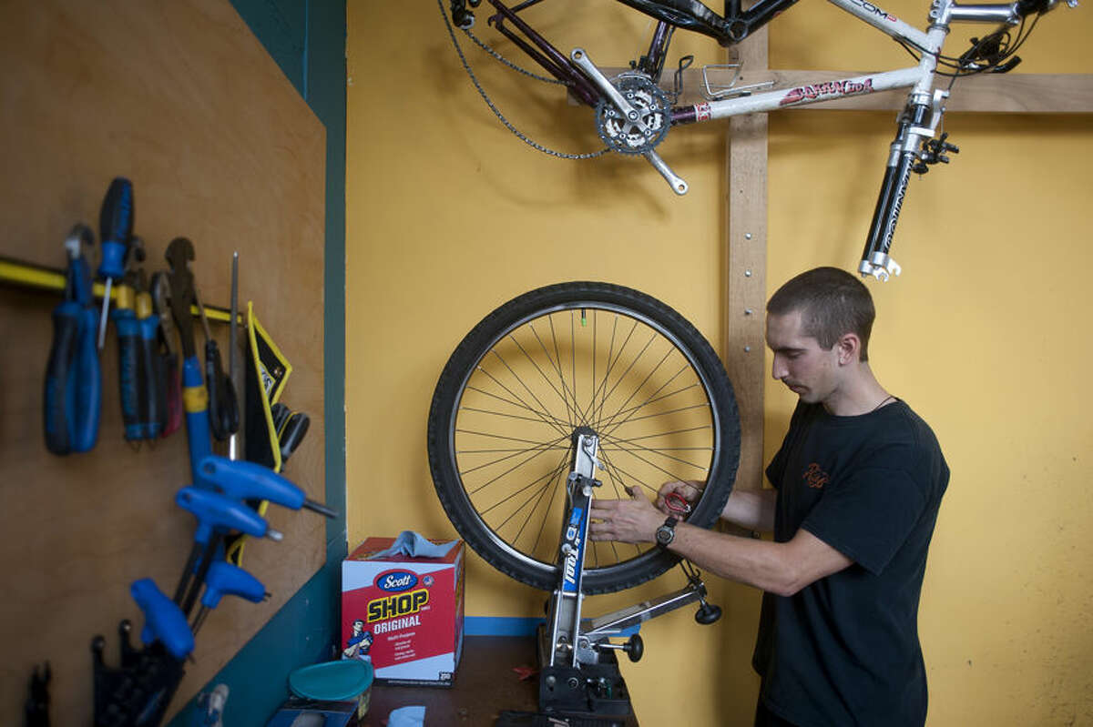 BRITTNEY LOHMILLER | blohmiller@mdn.net Joel Poliskey, a mechanic at Rays, trues a bike tire in the repair shop. Rays was awarded the best locally owned bicycle shop by the Midland Daily New's Reader's Choice awards.
