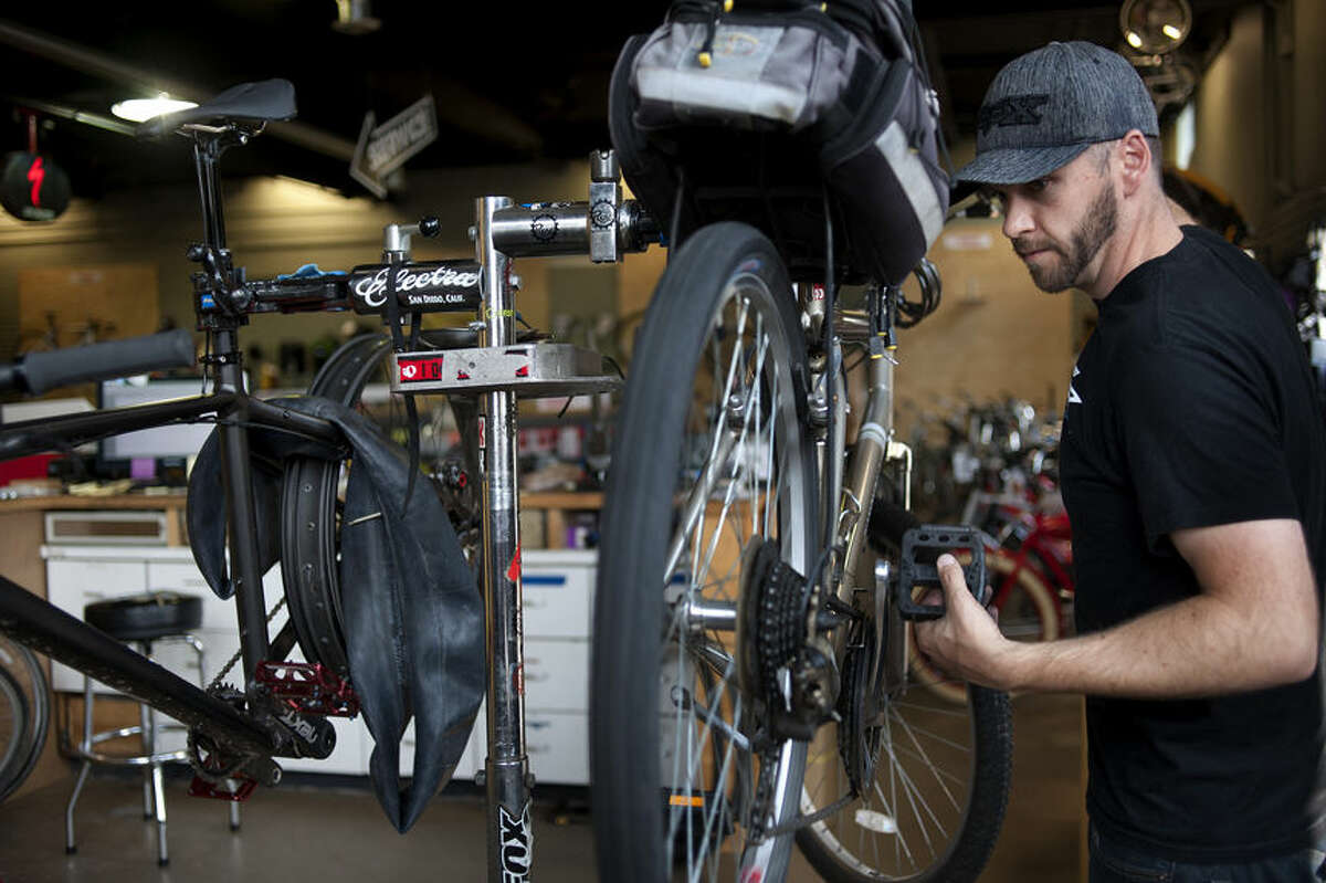BRITTNEY LOHMILLER | blohmiller@mdn.net Brad Alvesteffer, general manager at Rays, adjusts the shifting on a bike in the repair shop. Rays was awarded the best locally owned bicycle shop by the Midland Daily New's Reader's Choice awards.