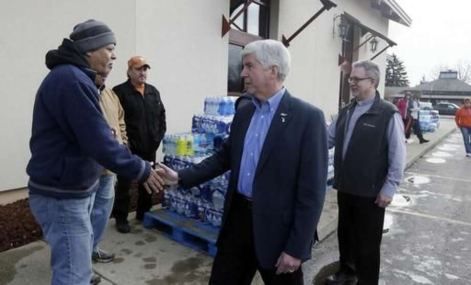 HOLD FOR STORY BY DAVID EGGERT- FILE- In a file photo from Feb. 5, 2016, Michigan Gov. Rick Snyder, center and Our Lady of Guadalupe Church Deacon Omar Odette, right, meet with volunteers helping to load vehicles with bottled water in Flint, Mich. Snyder's standing as one of the GOP's most accomplished governors has taken a beating in the lead-contaminated water emergency in Flint. Democrats, especially those running for president, are pointing to mistakes by Snyder's administration during the crisis as a vivid example of Republican-style cost-cutting run amok. (AP Photo/Carlos Osorio) Photo: Carlos Osorio