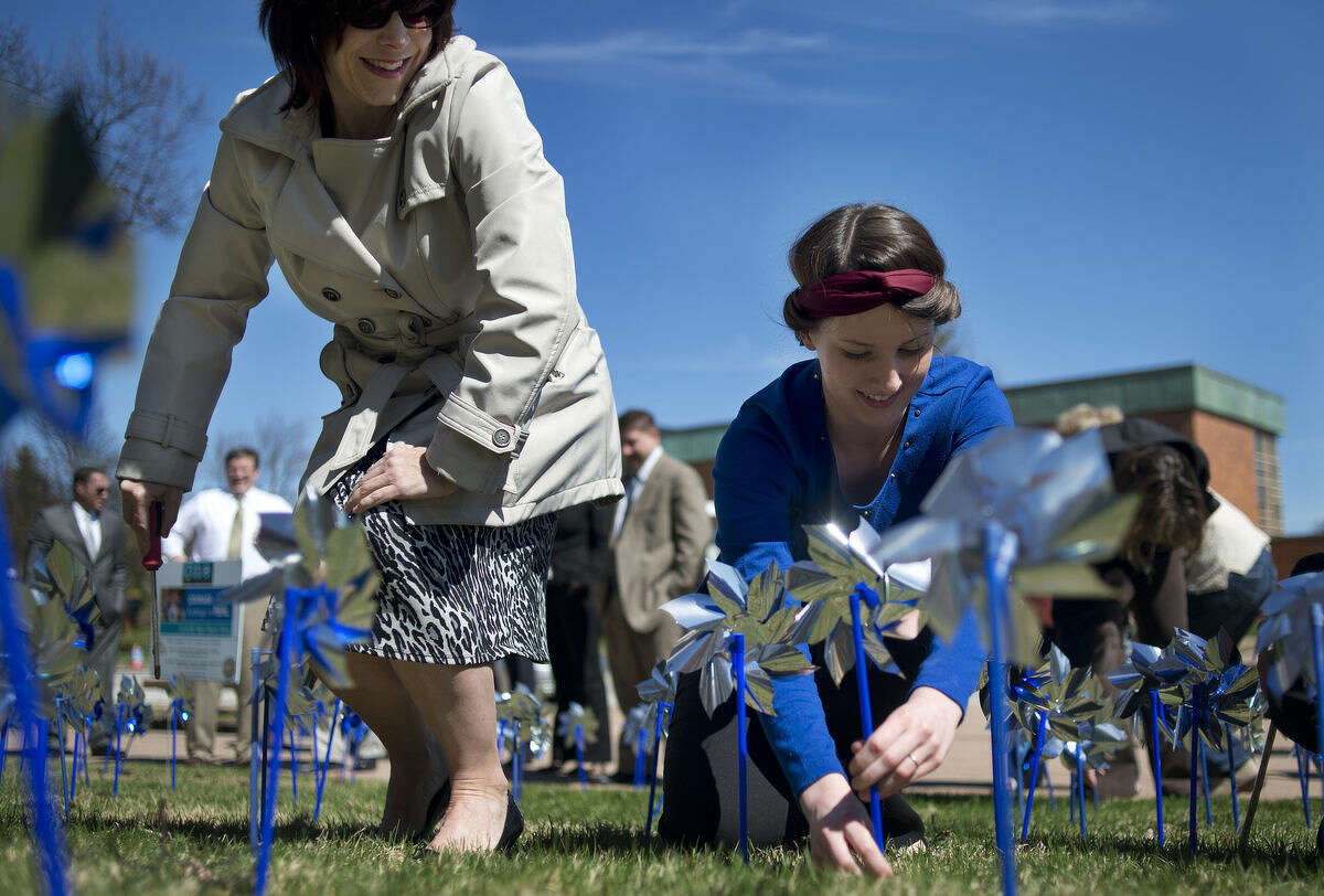 """Midland County Administrator/Controller Bridgette Gransden, left, and Mallory Flinn of Mt. Pleasant plant pinwheels in front of the Midland County Courthouse Wednesday afternoon in honor of Child Abuse Prevention Month. """"It's a beautiful thing,"""" Flinn, an intern for Big Brothers Big Sisters of the Great Lakes Bay Region, said. """"It's important to remember the whimsical nature a child's life is supposed to be, and that it sometimes gets taken for granted."""" This year 140 pinwheels were planted to represent the 140 child abuse cases Safe and Sound Child Advocacy Center had in 2014."""