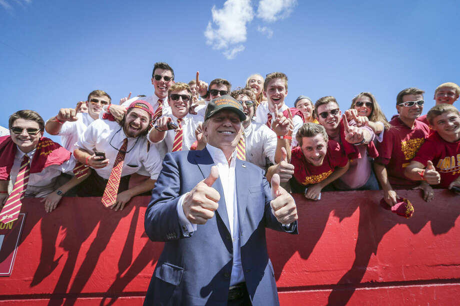 Republican presidential candidate Donald Trump poses for a photo with Iowa State fans before an NCAA college football game between Iowa State and Iowa, Saturday in Ames, Iowa. Photo: Rodney White | The Des Moines Register Via AP)