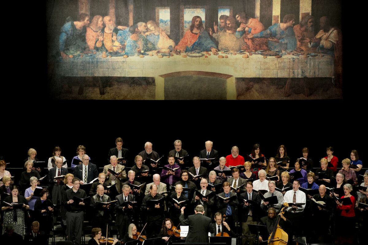 """The Center Stage Chorale sings a hymn under a full-scale replica of Leonardo da Vinci's """"The Last Supper"""" at the Midland Center for the Arts on Friday during a community wide Good Friday service. Rev. J. D. Landis of First United Methodist Church, Rev. Tom Schacher of Memorial Presbyterian Church, and Rev. Gerald Ferguson of Trinity Lutheran Church led the service."""