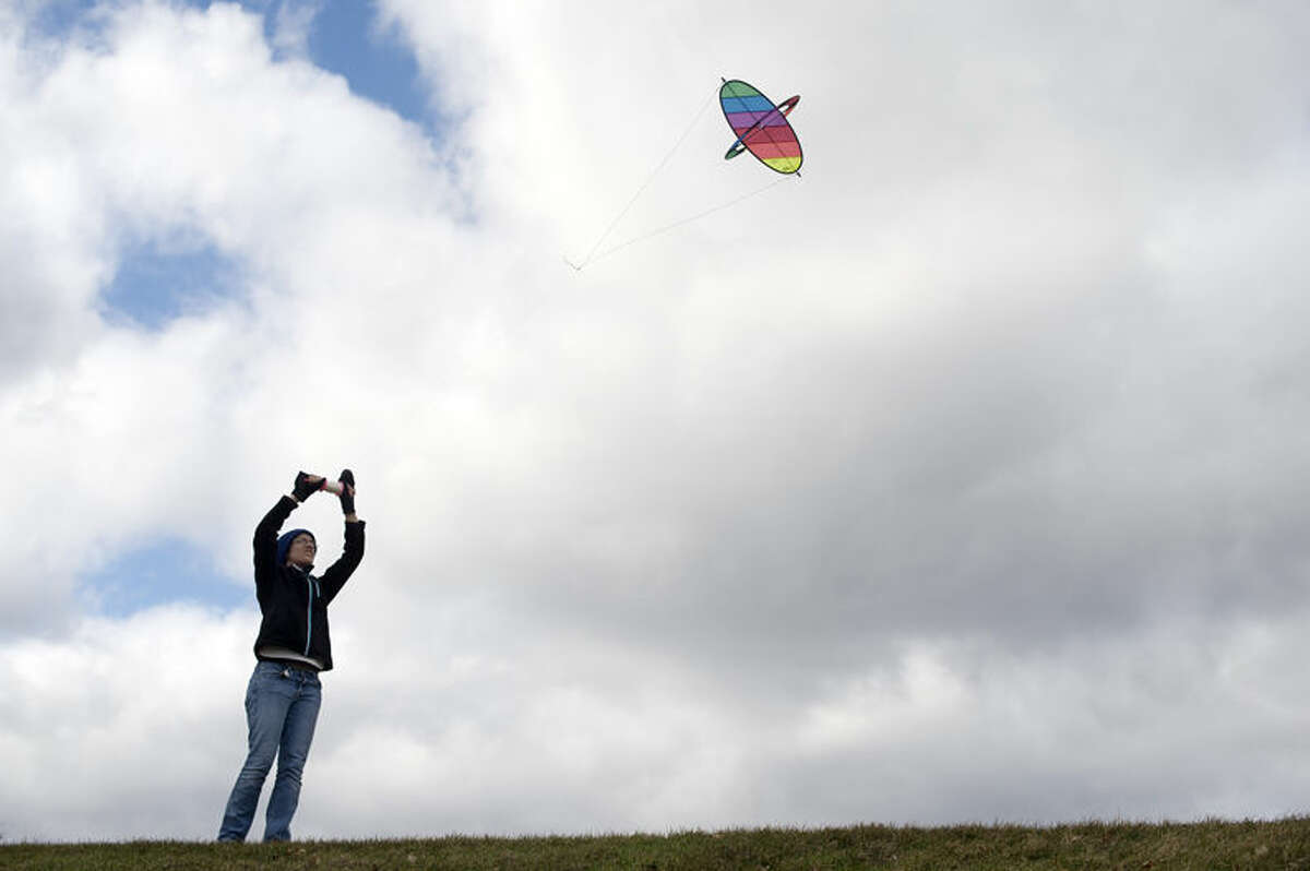 """Kayla Paulson of Midland flies her kite behind the former Central Middle School Friday afternoon. """"I woke up saw that it would be windy and I specifically packed it in the trunk of my car this morning,"""" Paulson said. """"You gotta take advantage of the wind."""""""
