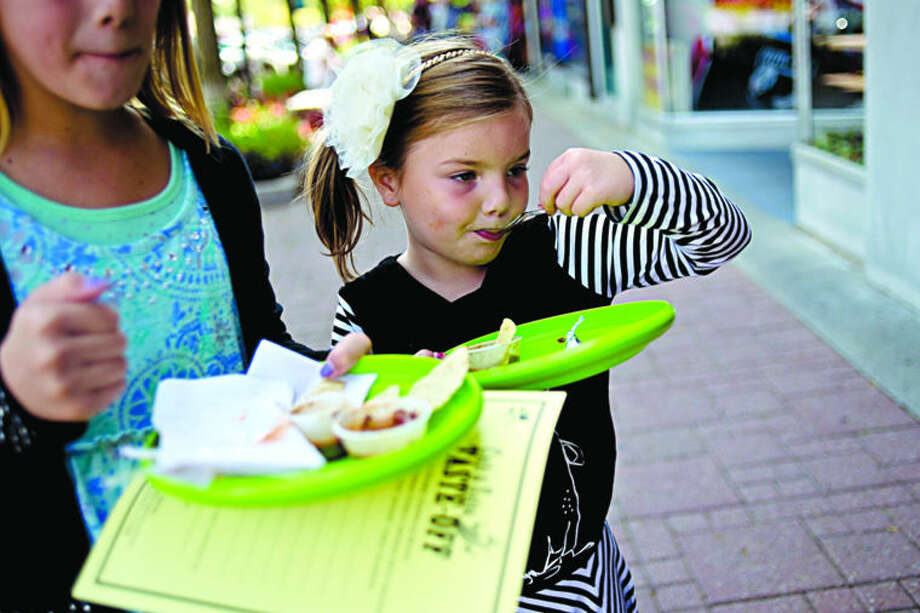 Avery Pfuehler, 6, right, and her sister Aly, 11, try a sample of chili during the 17th Annual Chili and Salsa Taste-Off on Saturday in downtown Midland. Photo: Nick King/Midland Daily News