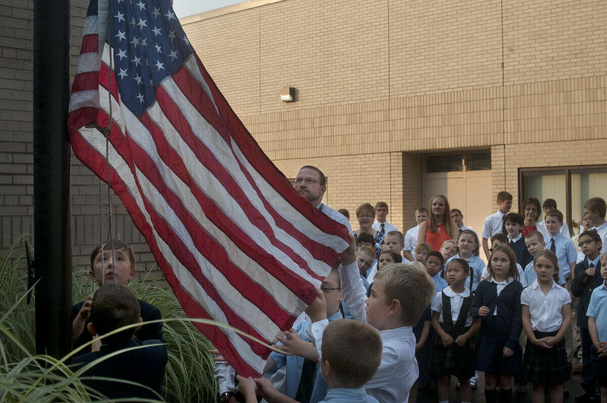 From left, fifth-grader Michael Wilkowski and third-grader Samuel Wilkowski raise the American flag while fourth-grader Zach Pider, third-grader Ciaran Knight and second-grader Caleb Pider unfold the flag outside of St. Brigid Catholic School on the first day of school before Mass.