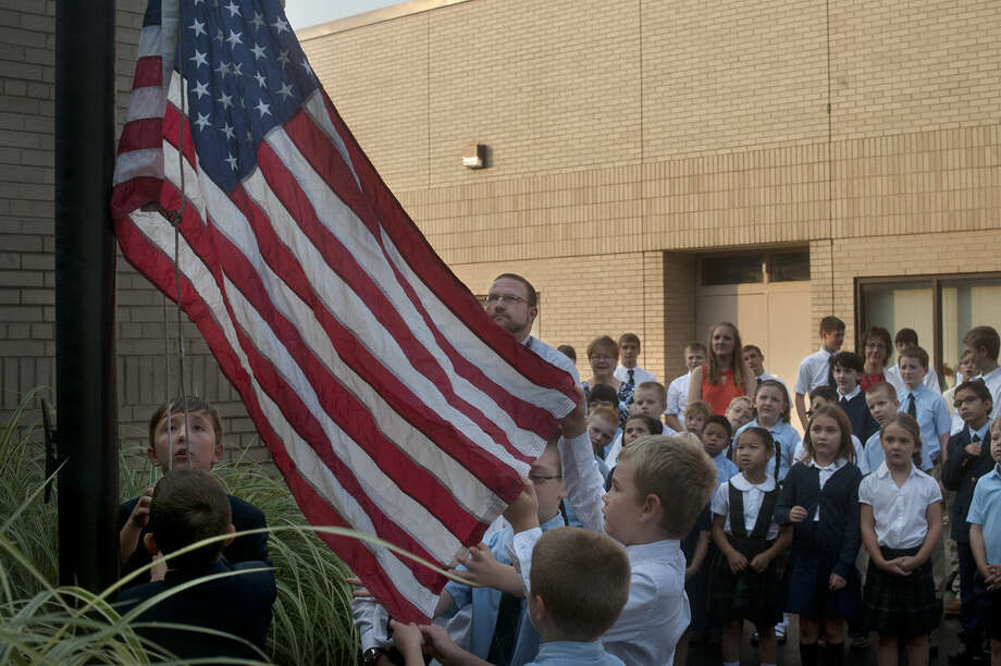 From left, fifth-grader Michael Wilkowski and third-grader Samuel Wilkowski raise the American flag while fourth-grader Zach Pider, third-grader Ciaran Knight and second-grader Caleb Pider unfold the flag outside of St. Brigid Catholic School on the first day of school before Mass. Photo: Brittney Lohmiller | Midland Daily News