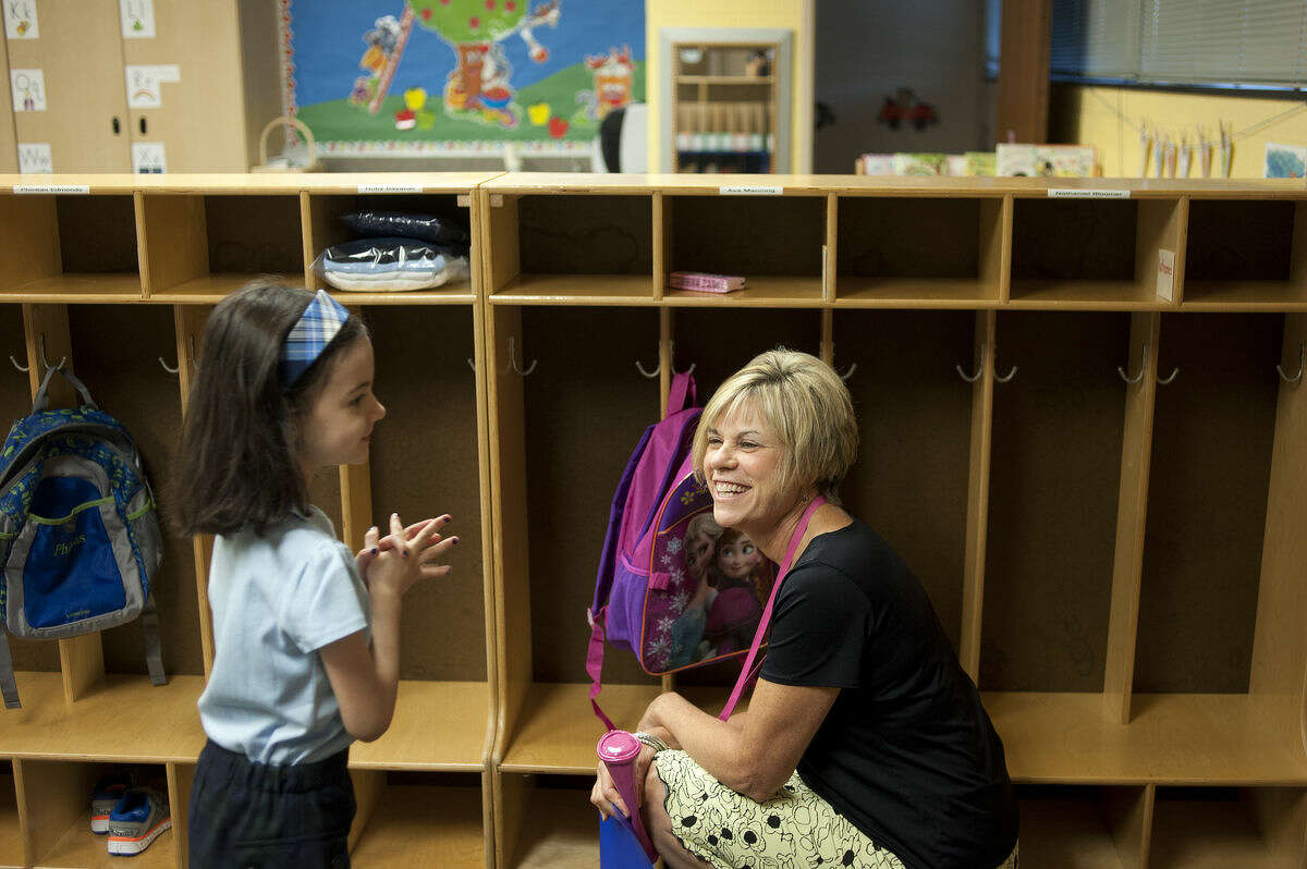 Kindergartener Ava Manning talks with her teacher Susie Hollingshead before the start of St. Brigid Catholic School's on the first day of school Wednesday morning.