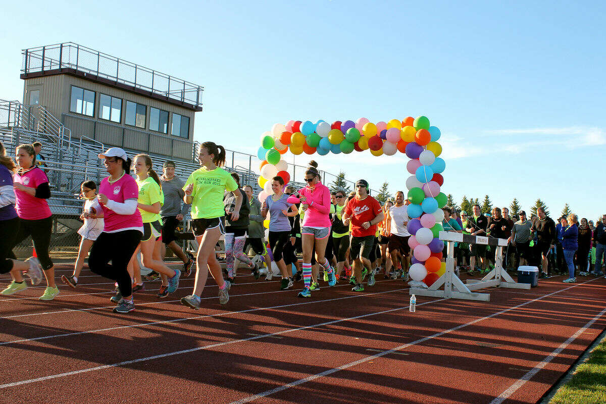 Runners take off from the starting line during the #LIVELIKEREED Glow Run at CMU's outdoor track Saturday night.