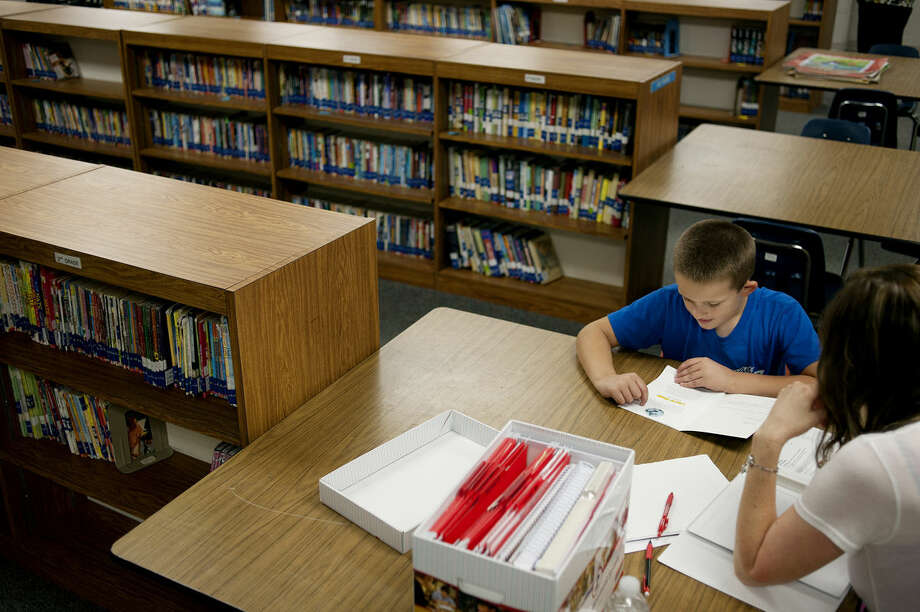 Coleman Elementary technology teacher Margie Hintz works with 9-year-old Adam Clarke inside the newly remodeled library at the school. Photo: Brittney Lohmiller | Midland Daily News