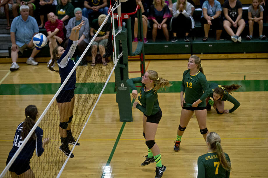Dow High's Carley Hitt spikes the ball over the net and through Mount Pleasant opponent Carli Taylor's fingers in the second set of the match on Tuesday at H.H. Dow High School. Photo: Erin Kirkland | Midland Daily News