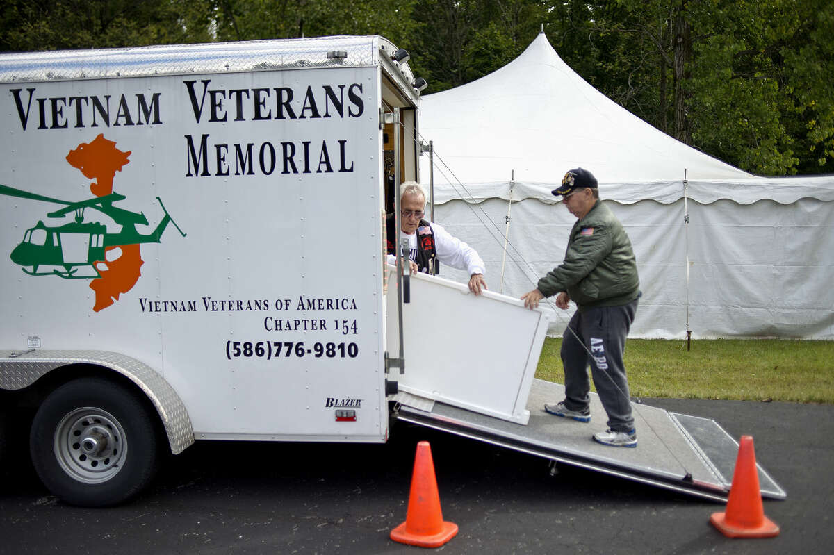 Vietnam Veterans of America Chapter 154 members Mike Schneider, left, and Robert Steward, both of Mount Clemens, start unpacking the Michigan Vietnam Veterans Traveling Memorial Wall at the Sanford American Legion Post last year. The Wall is returning to Sanford this year on Saturday and Sunday