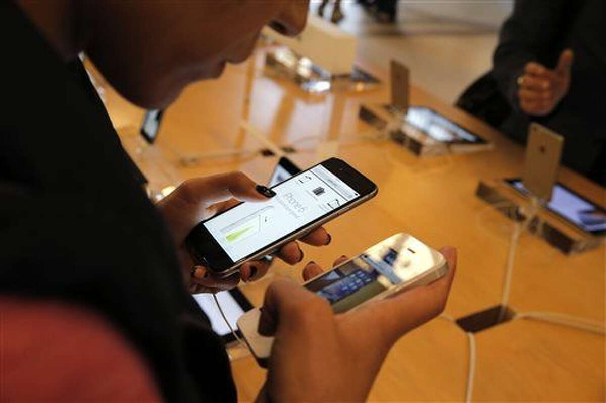 In this file photo, a customer checks out the new iPhone 6 at an Apple store in Paris. Apple's iPhones and iPads are getting free software updates today, including battery improvements and a smarter virtual assistant.