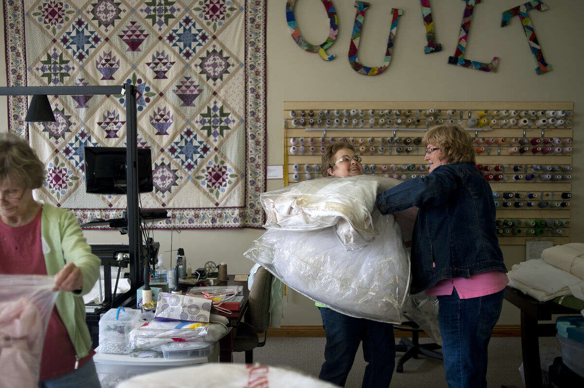 Carol Gilmour of Saginaw, left, unpacks a donated wedding dress while Deb Kraft of Gladwin, right, gives Debbie Crosby of Saginaw, center, a wedding dress to put in the storeroom at Miles of Stitches in Merrill Thursday afternoon. Once a month, members of Angel Gowns of Michigan meet to transform donated wedding dresses into burial gowns for infants who have passed away.
