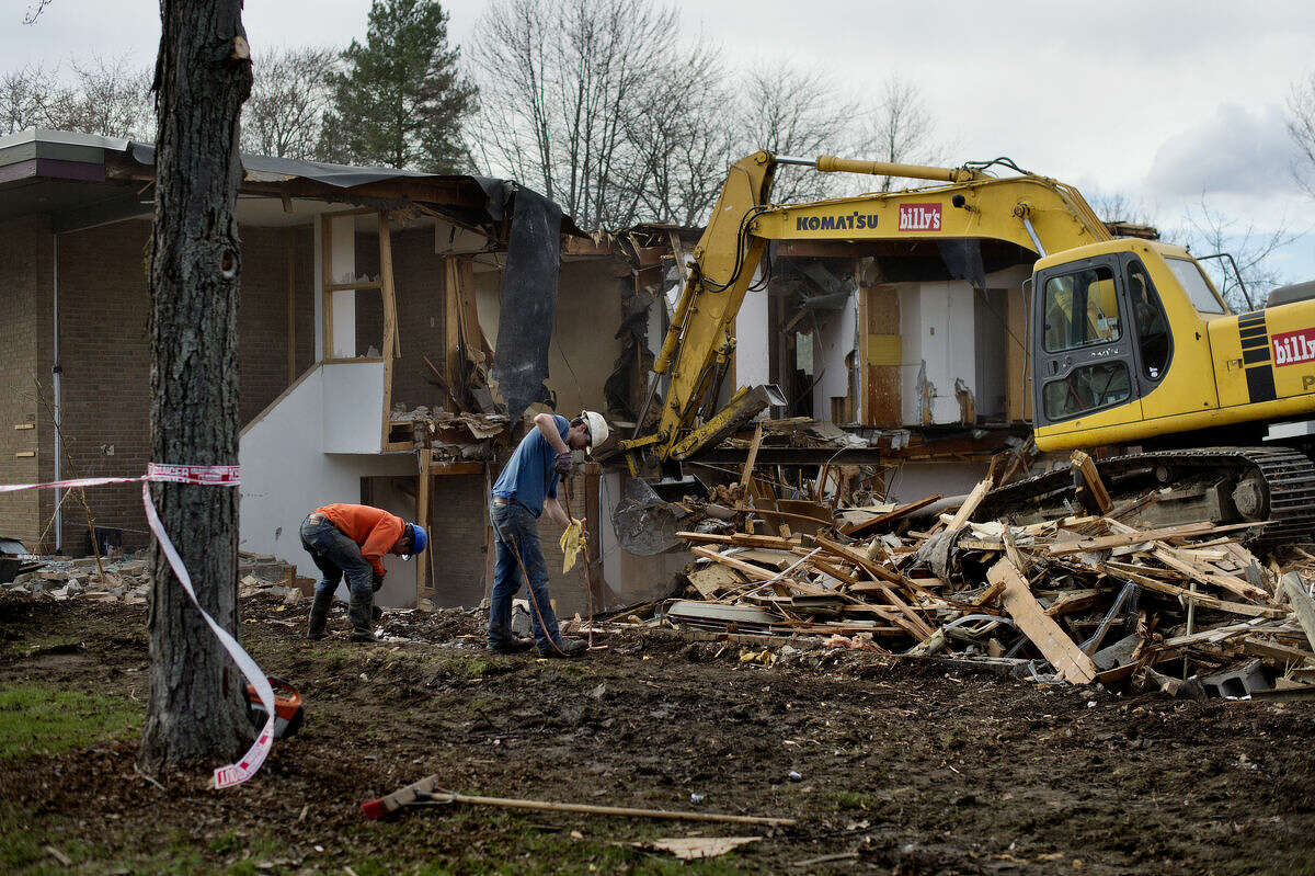 A crew works to demolish a building on Sugnet Road next to LaLonde's Market on Monday afternoon in Midland. A shortage of parking has seen LaLonde's purchase and demolish the old Northwood University administration building next door.