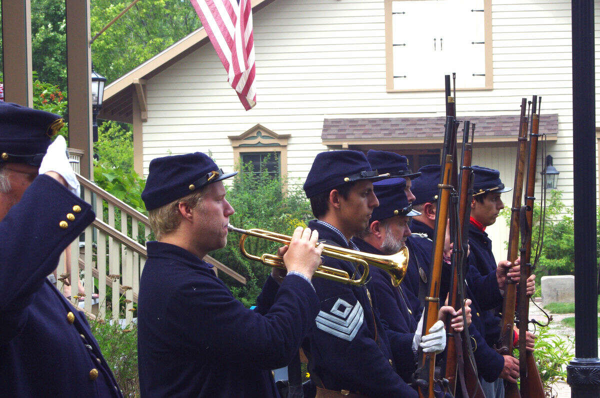 A bugler plays his instrument as an officer salutes and other re-enactors present arms last August near the Bradley Home in the Midland County Historical Society's Heritage Park. The ceremony was part of Civil War Family Day, attended by more than 200 people. The event was presented by the Tenth Michigan Infantry re-enactment group and the Midland County Historical Society with help from the Michigan Humanities Council.