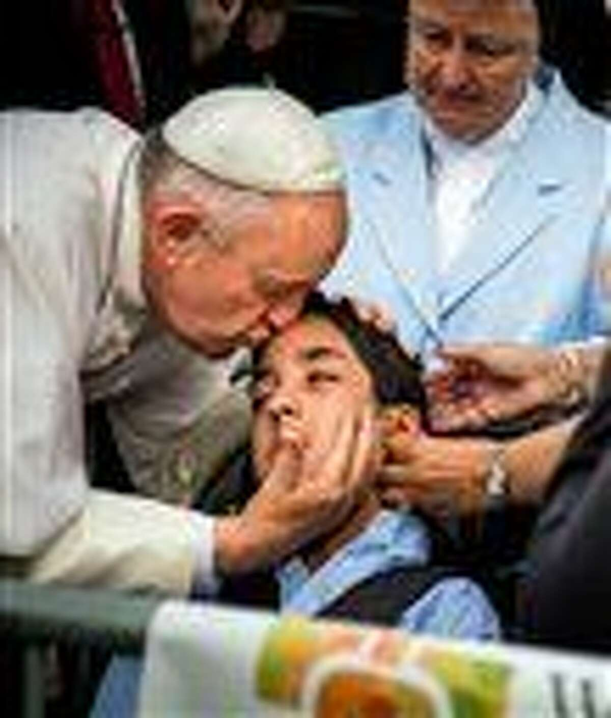 In this photo provided by World Meeting of Families, Pope Francis kisses and blesses Michael Keating, 10, of Elverson, Pa after arriving in Philadelphia and exiting his car when he saw the boy, Saturday, Sept. 26, 2015, at Philadelphia International Airport. Keating has cerebral palsy and is the son of Chuck Keating, director of the Bishop Shanahan High School band that performed at Pope Francis' airport arrival. (Joseph Gidjunis/World Meeting of Families via AP) MANDATORY CREDIT