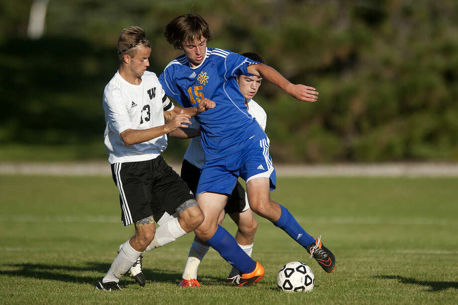 Thomas Schwartz of Midland dribbles around Alex Topping, left, and Zach Houlihan of Bay City Western in the second half of the Wednesday evening game in Auburn. Midland defeated Western 2-1. Photo: Brittney Lohmiller   Midland Daily News