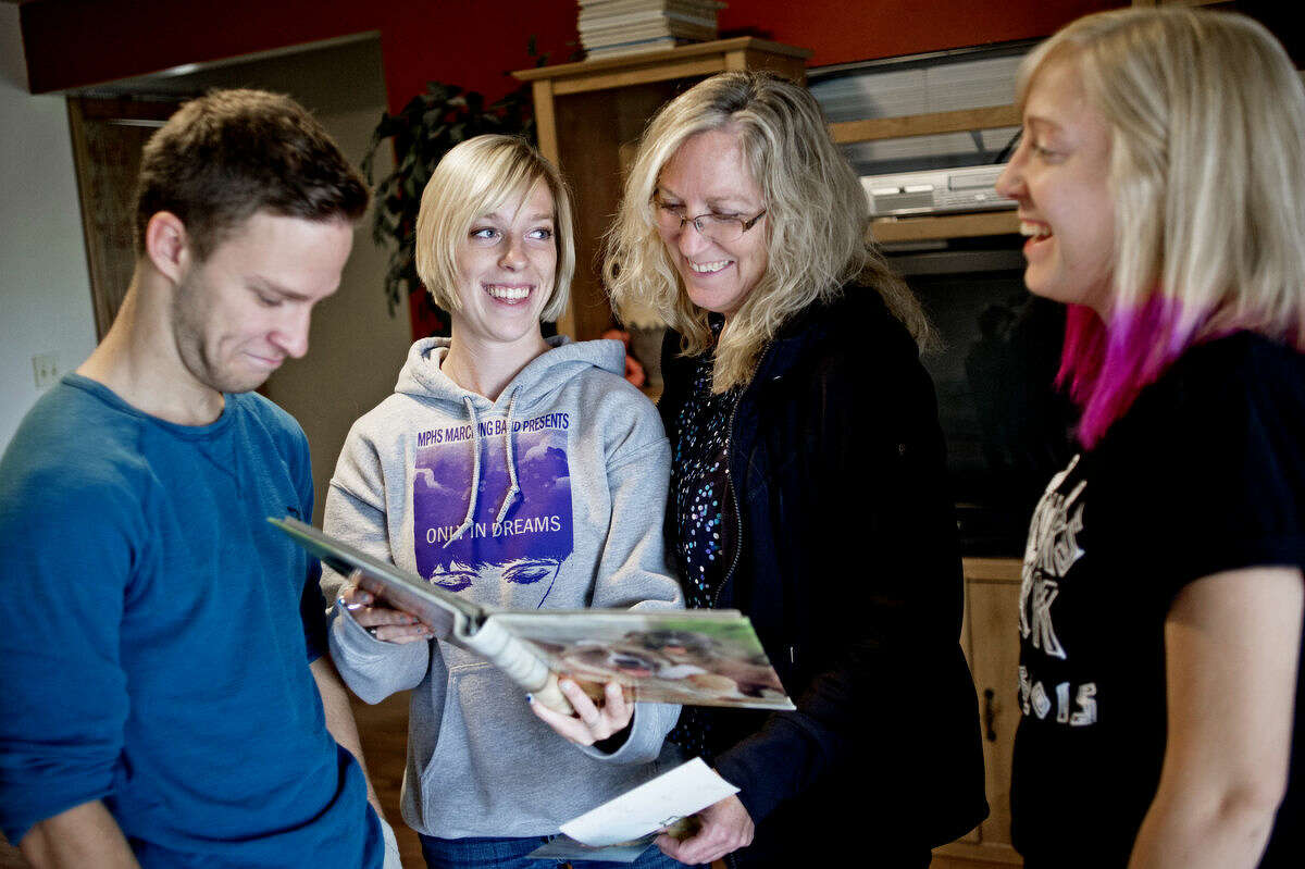 Riley Aultman, 18, left, frowns as sister Nicole Autlman, 18, mother Barb Aultman and sister Chelsea Aultman, 18, laugh at his baby pictures in Mount Pleasant on Tuesday after helping Chelsea pack up to move to Davenport University in Grand Rapids where she will study business. All three siblings were born prematurely as quadruplets in 1997. Sister Kayla Aultman died at 18 months due to complications from her premature birth.