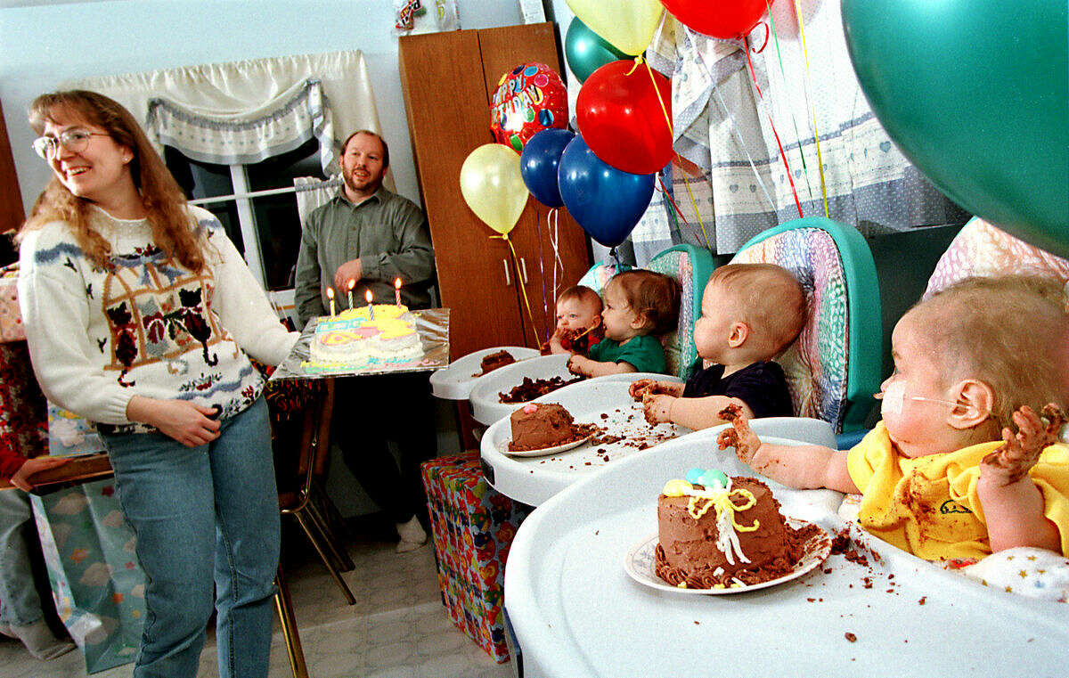 """In this Daily News file photo from 1998, Barb Aultman, left, holds out the cake as family and friends start to sing """"Happy Birthday"""" during the quadruplets' first birthday party."""