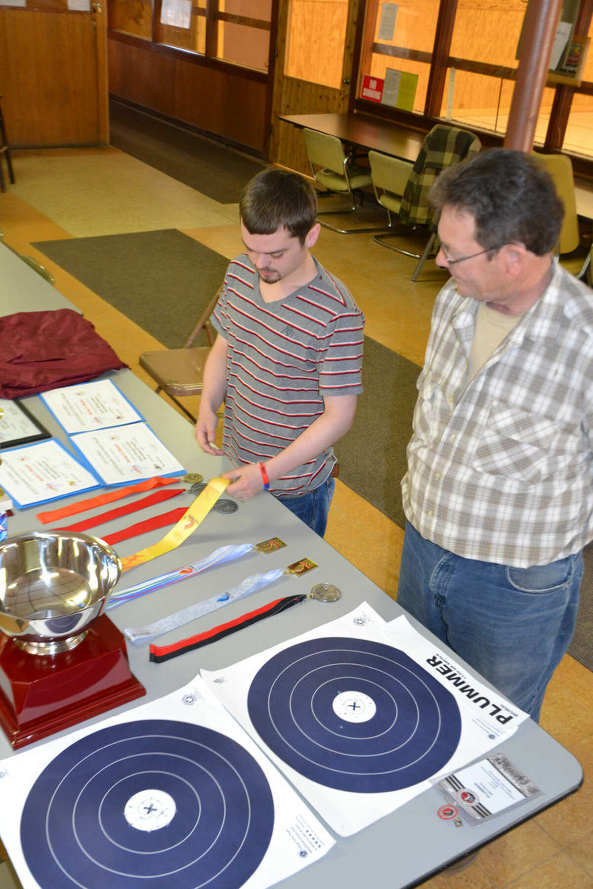 Michael Plummer and his dad, Steve Plummer, look at various archery awards. Steve also is a tournament archer. He placed third in his division at the Indoor Nationals.