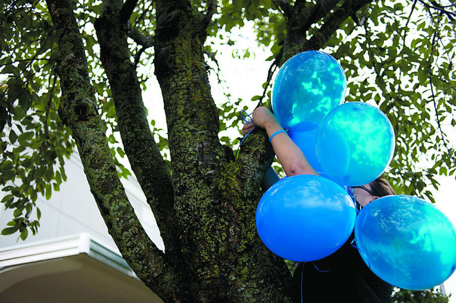 BRITTNEY LOHMILLER | blohmiller@mdn.net Amanda Oster ties blue balloons in a show of appreciation for law enforcement officers around Midland Friday afternoon. Oster along with Judi McAtmney and Mary Fisher hung over 300 balloons around Midland as well as giving local police donuts. Photo: Brittney Lohmiller/Midland Daily News