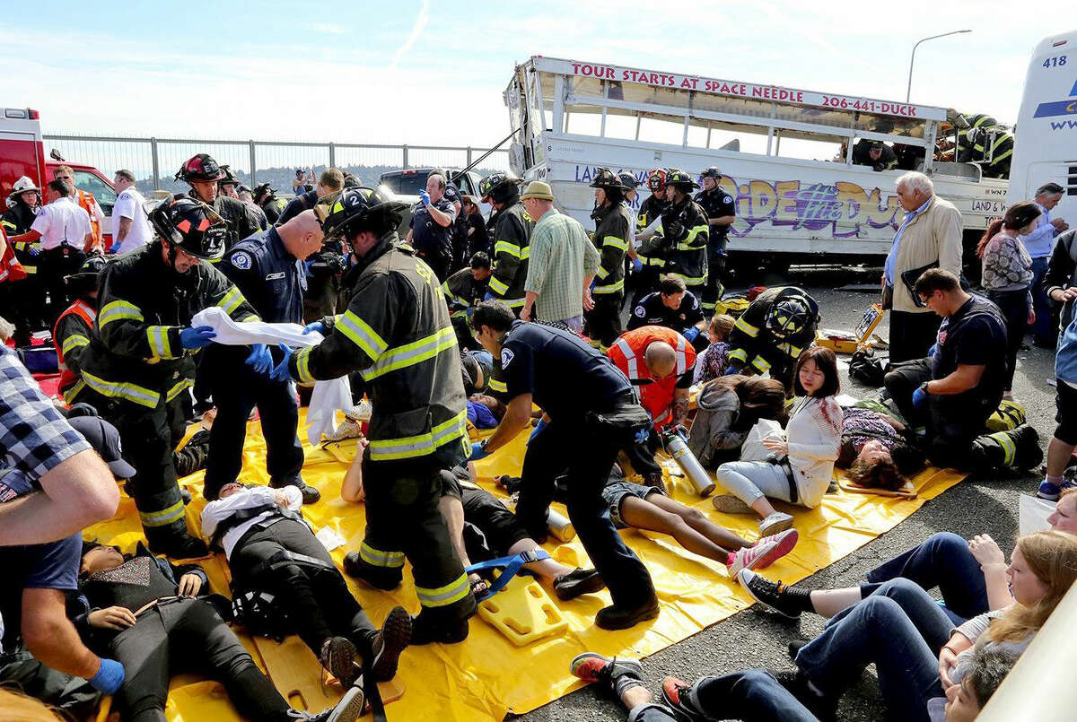 """Emergency personnel work at the scene of a fatal collision involving a charter bus, background, and a """"Ride the Ducks"""" amphibious tour bus, right, on the Aurora Bridge in Seattle on Thursday."""