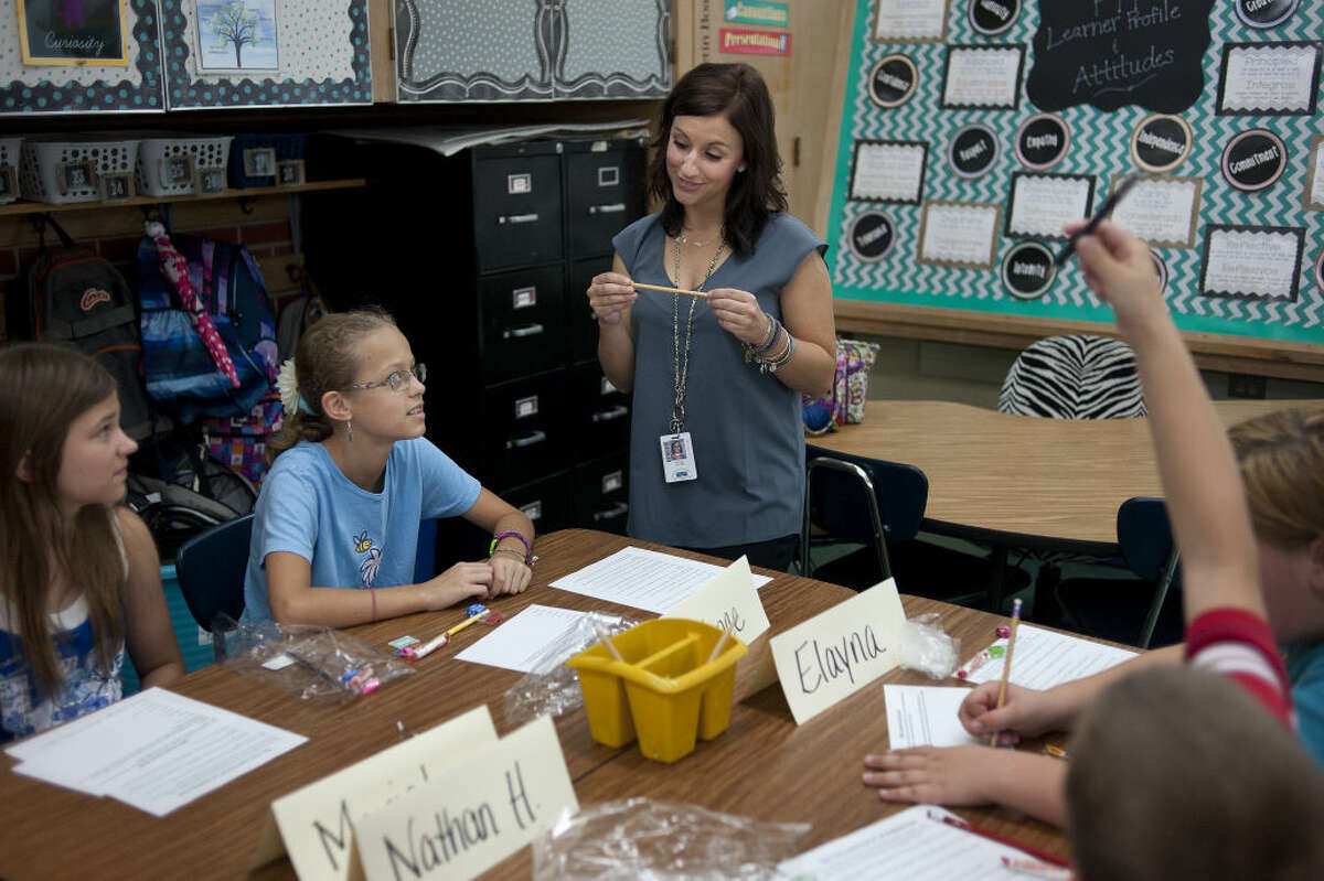 Fifth grade teacher, Whitney Jacobs, talks to her students Moriah Jacobson, from left, Kadence Keegstra, Nathan Holmes and Elayna McReynolds about why a pencil was included in their fifth grade survival kit on the first day of school at Plymouth Elementary Tuesday morning.