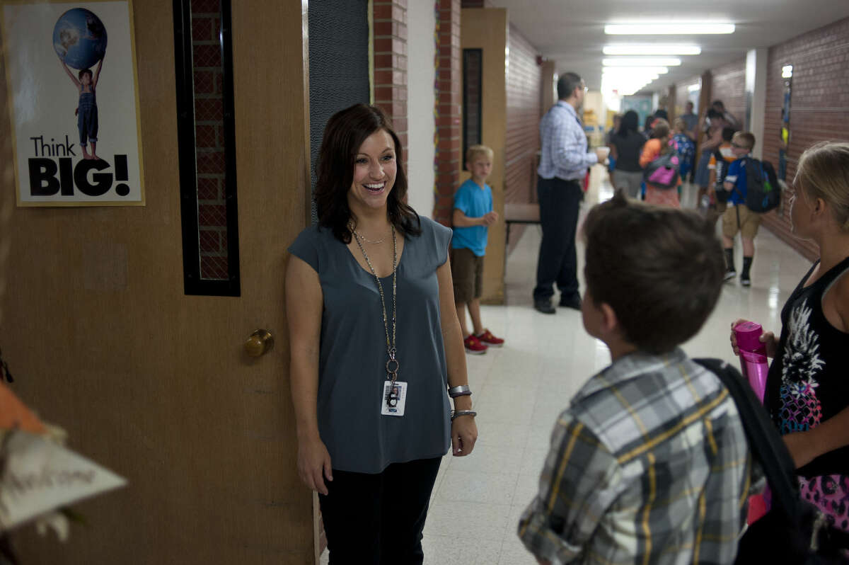 Fifth grade teacher, Whitney Jacobs, greets students as they enter her classroom on the first day of school at Plymouth Elementary Tuesday morning.