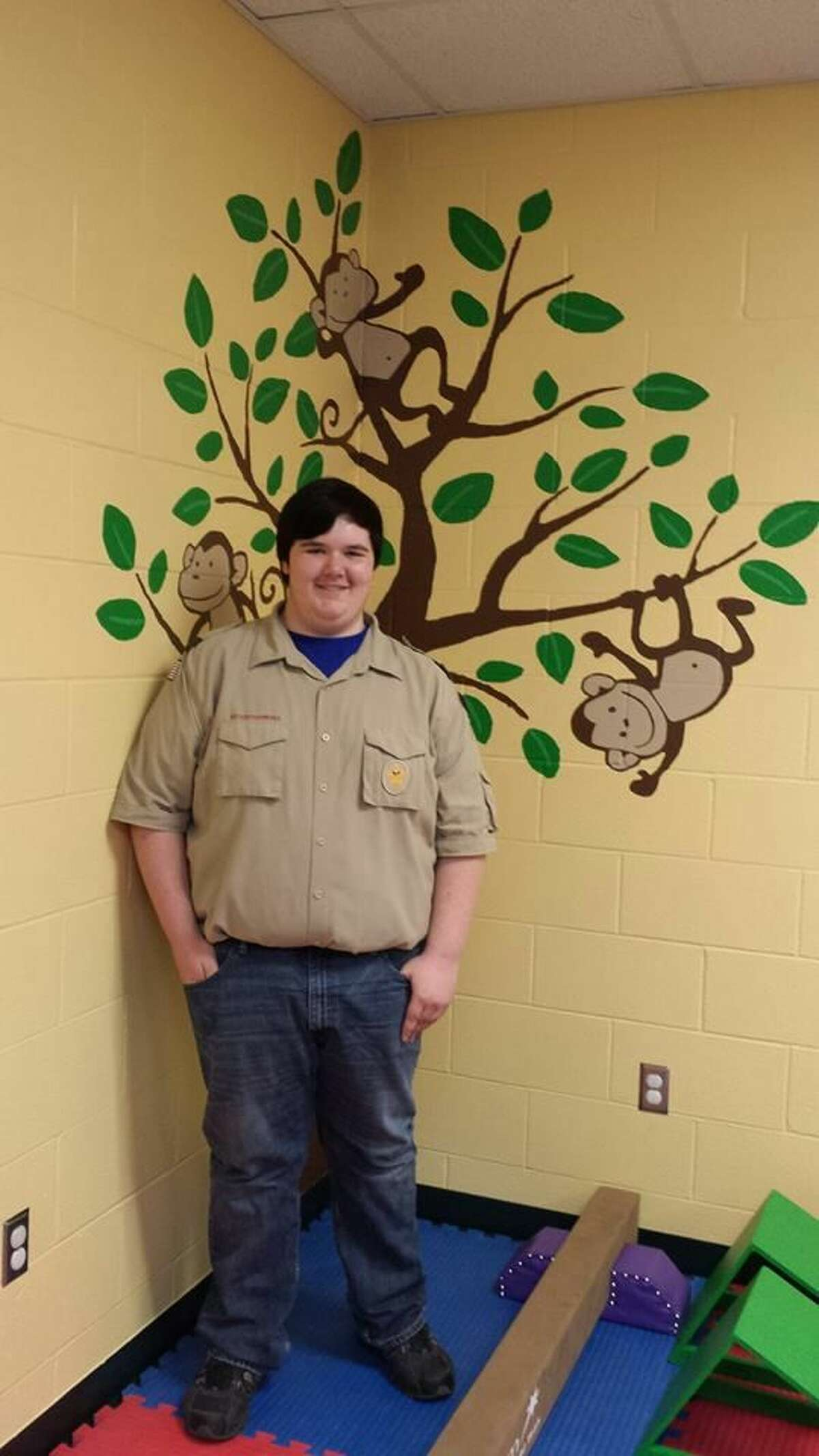 Eric Nesbitt is shown with a mural he painted.