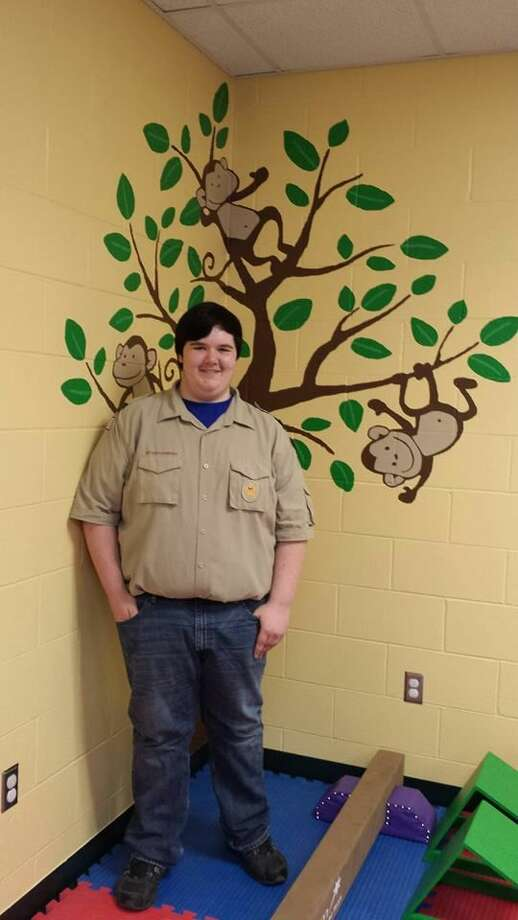Eric Nesbitt is shown with a mural he painted. Photo: Photo Provided